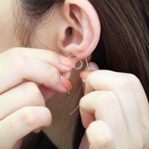 樹脂ノンホールピアスを両手で耳たぶに挟み込む